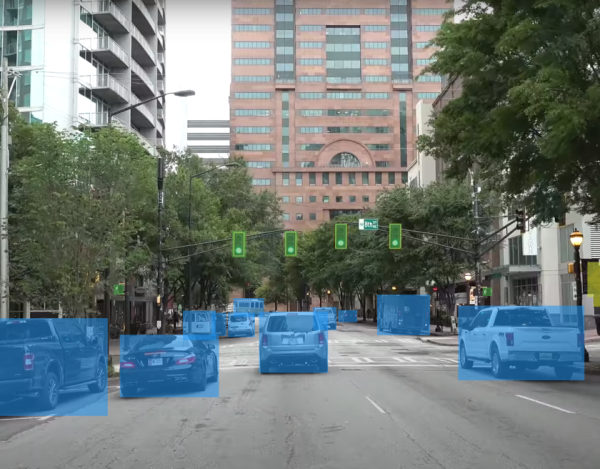 A frame from the camera of a self-driving vehicle with salient items on the road like traffic lights and other vehicle highlighted